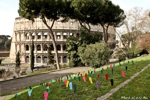Sandálias escoltadas pelo Coliseu, em Roma